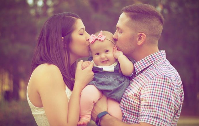 Couple Kissing Baby While Carry