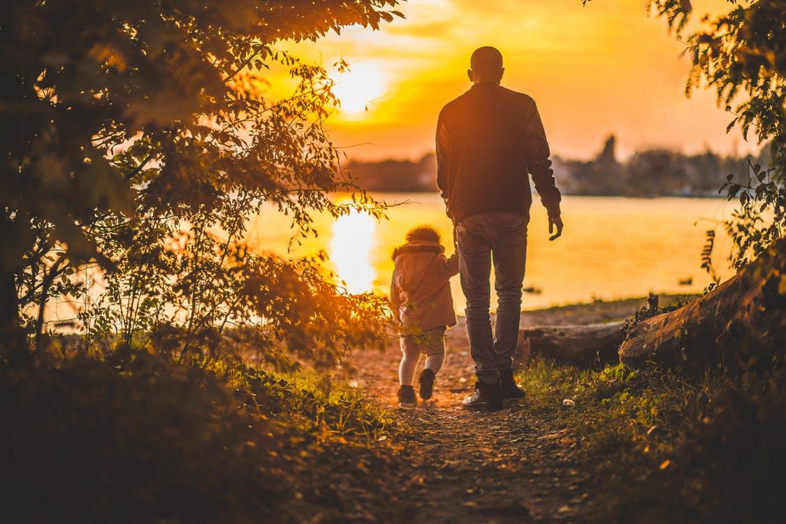Portrait Photography of Man Holding a Child